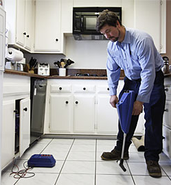 a plumbing contractor searches for an underfloor leak with an electronic dectector